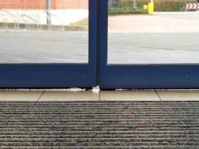 Schiebetür einer Einzelhandelsfiliale mit undichten Türbürsten.